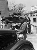 1930s Service Station Attendant in Cap and Coveralls Pouring Water from Spouted Can into Automobile