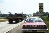 1970s Police Car with Radar Gun Checking for Speeders in 55 Mph Speed Zone