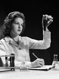 1940s Student Nurse Holding Up Test Tube While Taking Notes in Science Class