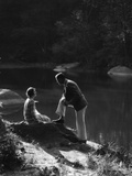 1920s-1930s Woman Sitting on Rock Lakeside Talking to Man