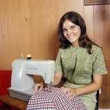 1970s Young Woman Teenager Using a Singer Sewing Machine Looking at Camera