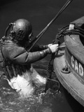 1930s Side View of Diver in Pressure Suit Descending into Water from Side of Boat