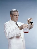 1960s Man Wearing Lab Coat Pouring Liquid from Small Erlenmeyer Flask into a Larger Flask