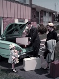 1950s Family Mother Father Daughter in Front of Suburban House Packing Luggage in Car for Vacation