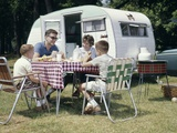 1960s Family Sitting in Lawn Chairs at Picnic Table Beside Camping Trailer