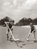 1930s-1940s 2 Boys with Sticks and Puck Wearing Roller Skates Playing Street Hockey