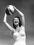 1940s Woman in White Bathing Suit Holding a Beach Ball over Her Head Outdoor