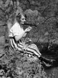 1920s Young Woman in Striped Skirt Sitting on Stream Bank in Woods Braiding Garland of Wild Flowers
