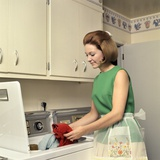 1970s Woman Housewife Homemaker Wearing Apron Loading Laundry into Washing Machine