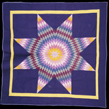 An Amish Pieced and Quilted Cotton Coverlet Worked in a Multicolored Lone Star on a Navy Background