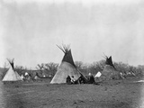 A Native American Family Sits Outside their Teepee