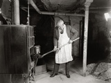 1940s Elderly Man Shoveling Coal into Furnace in a Basement