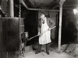 1940s Elderly Man Shoveling Coal into Furnace in a Basement