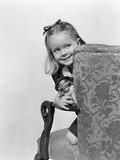 1940s Little Girl Holding Doll Peeking around Side of Chair