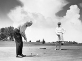 1960s Older Couple on Golfing Green Man Putting