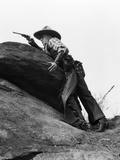 1920s Cowboy Among Rocks Aiming Revolver