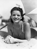 1930s Teen Girl Lying on Beach under Umbrella Wearing Bathing Suit Smiling