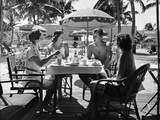 1930s Three Women and One Man Sitting at Tropical Pool Side Table Talking Together
