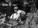 1920s Boy Putting Toy Sailboat into Stream