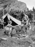 1920s-1930s Two Men and One Woman Eating a Meal around a Campfire with a Tent and Horses