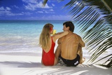 Couple on Tropical Beach with Palm Frond Ocean and Sky