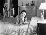 1940s Fully Dressed Smiling Woman Laying on Her Bed with Her Legs Up Reading a Letter