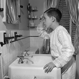 1950s Boy Combing Hair Looking in Bathroom Sink Mirror