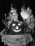 1920s-1930s Couple in Costumes Looking Down into Candle Light from Carved Pumpkin Jack-O-Lantern