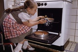 Girl Wearing Apron Removing Cakes from Oven