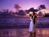 Dressed Up Couple Embracing on the Beach at Sunset