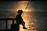 Silhouette of Child Fishing Off a Dock at Sunset