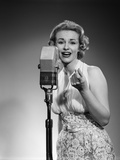 1950s Portrait of Woman Singing into a Microphone