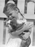 1930s-1940s 1950S Little Girl with Braids Holding a New Puppy Dog