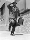 1950s-1960s Frantic Man Running Down Street Holding Hat on with Hand Carrying Briefcase