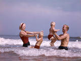 1970s Family Laughing Hand Holding Jumping in Ocean Surf at Beach