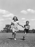 1940s Two Smiling Children Running Holding Hands in Grassy Field
