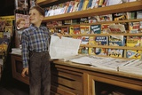Boy Holding Paper in Newsstand
