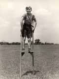 1930s-1940s Smiling Happy Boy Wearing Striped Shirt and Short Pants Walking on Pair of Stilts