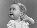 1940s-1950s Close-Up Portrait of Baby Girl with Curl on Top of Head with Hand Held Up Beside Ear
