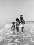 1970s African American Family Wading in Surf Walking Along Beach Together