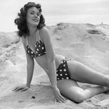 1950s-1960s Brunette Bathing Beauty Stretched Out on Sand Wearing Polka-Dot Bikini
