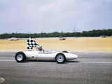 1960s Race Car Driver in Lotus Ford Car Taking Victory Lap Holding Checkered Flag