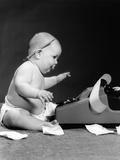 1960s Side View of Chubby Baby Seated Behind Adding Machine with Pencil Behind Ear