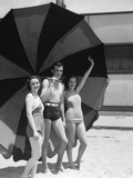 1930s Two Women One Man Smiling Wearing Bathing Suits Standing under Beach Umbrella