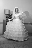 1950s-1960s Bride in Full Gown Veil and White Gloves Standing in Room with Open Door