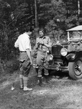 1920s-1930s Couple in Fishing Gear Holding Poles Standing in Front of Packard Touring Automobile