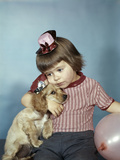 1950s-1960s Little Girl Wearing Party Hat Frowning Hugging a Cocker Spaniel Puppy