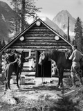 1920s-1930s Couple in Front of Log Cabin Standing by Horses with Saddles Both Wearing Jodhpurs