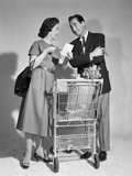 1950s Couple Man Woman Shopping Cart Reviewing Grocery List Man Has Cigar in Hand