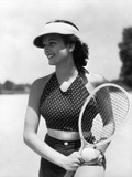 1930s Woman in Polka Dot Halter Top Shorts and Sun Visor Holding a Tennis Ball and Racket